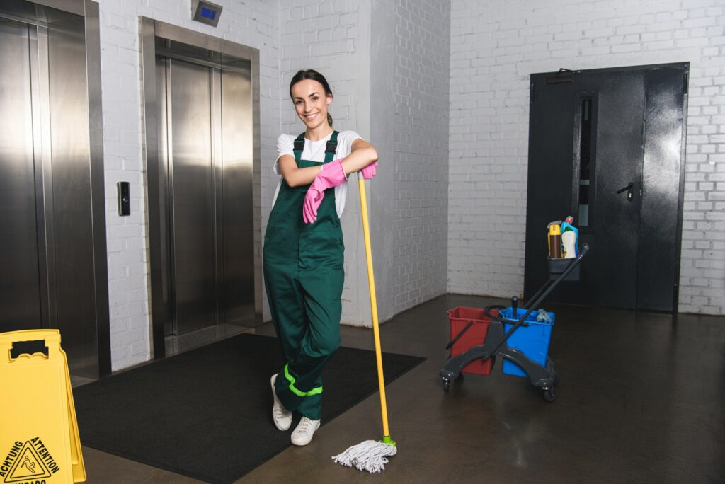 beautiful young janitor leaning at mop and smiling at camera